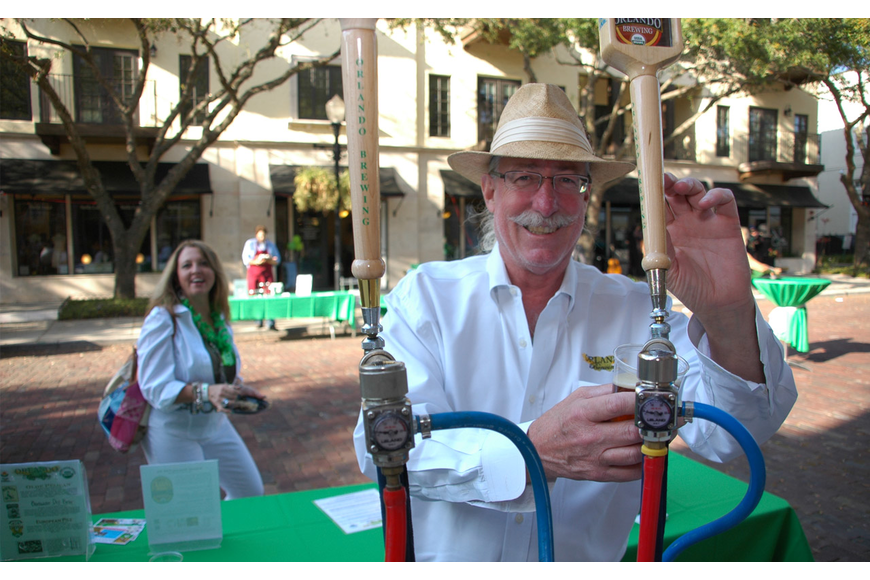 Photo by: Isaac Babcock - Orlando Brewing Company President John Cheek pours a pint at The Hannibal Square Wine Tasting & St. Patrick's Day Street Party on March 17 on New England Avenue.