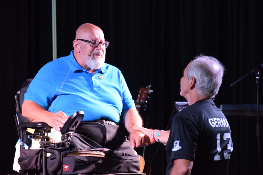 "Keynote speaker Bob ""Mr. Inspiration"" Wieland shakes hands with Robbie German's father, Tim."